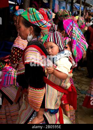 Flower Hmong woman carrying baby on her back, Bac Ha Sunday Market, Lao Cai Province, Vietnam - Stock Photo