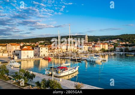 Supetar on Brac Island near Split, Croatia. Small seaside town with promenade and harbor with white boats, palm trees, cafes, houses and church. Touri
