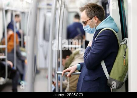 Ill man in eyeglasses feeling sick, wearing protective mask against transmissible infectious diseases and as protection against coronavirus, covid-19 - Stock Photo