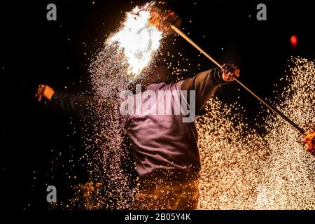 A close up energetic shot of a fire dance performer using a long flaming pole to create flying embers and light effect. during a multicultural festival - Stock Photo