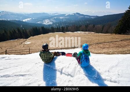 Top view of two snowboarders resting, sitting on snowy summit enjoying beautiful view on background of blue sky and mountain peaks on sunny winter day. Extreme winter sports, active lifestyle concept. - Stock Photo