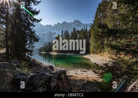 View on the mountain side from the shore of the lake named Eibsee on a sunny afternoon. - Stock Photo