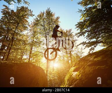 Young male cyclist jumping on trial bicycle between two big boulders, professional rider making acrobatic trick in the forest on sunny day. Concept of extreme sport active lifestyle - Stock Photo