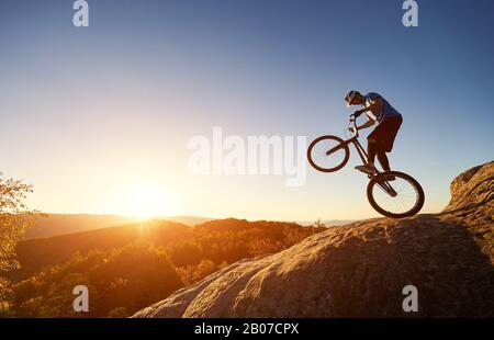 Silhouette of cyclist balancing on back wheel on trial bicycle. Courageous sportsman biker making acrobatic trick on top of rocky mountain at sunset. Concept of extreme sport active lifestyle - Stock Photo