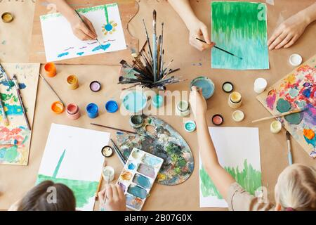 High angle view of group of children painting their pictures with watercolor paints during art lesson