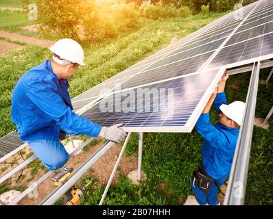 Installing of stand-alone solar photo voltaic panel system. Two technicians in hard-hats mounting big shiny solar module on platform on green summer view background. Alternative energy concept. - Stock Photo
