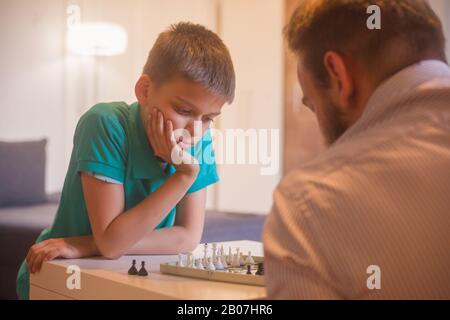 young man and son playing chess together. Son is thinging about his next move.
