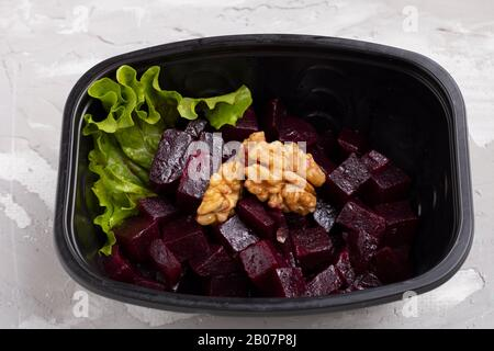Beets, raw nuts, Turnips, greens and Onion Salad in food container, close up - Stock Photo