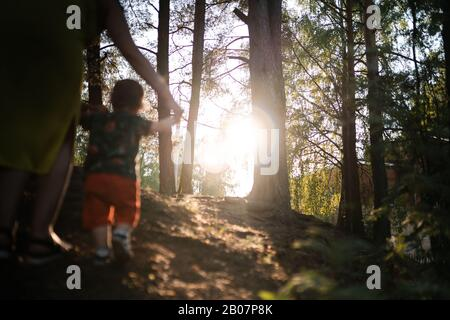 Mother walking playing baby child boy in forest wood - Young mom in green dress and her baby in a green park having fun - Happy smiling people