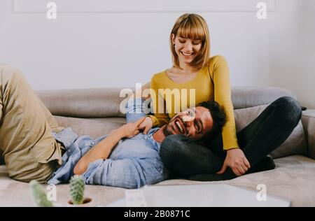 Young couple spending time together at home. Man and woman sitting on the couch and having fun - Stock Photo