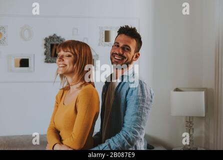 Young couple spending time together at home. Man and woman dancing in the living room and having fun. - Stock Photo