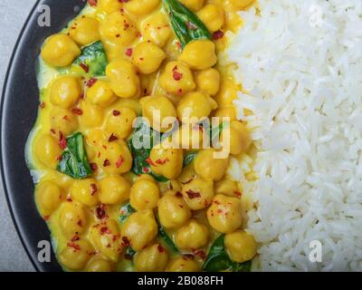 rice, chickpeas with coconut milk and curry. vegetarian dish - Stock Photo
