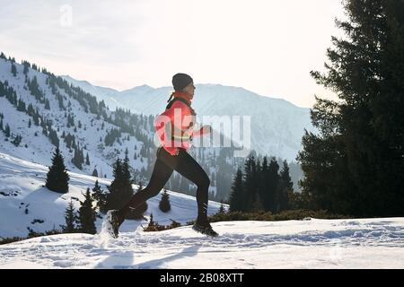 Trail runner in pink jacket woman running in winter mountains trail on snow.