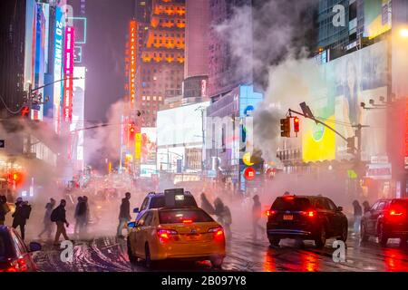 The drifting steam surrounds people, traffic and Times Square buildings in the snowy night at Midtown Manhattan New York City NY USA on Jan. 18 2020 - Stock Photo