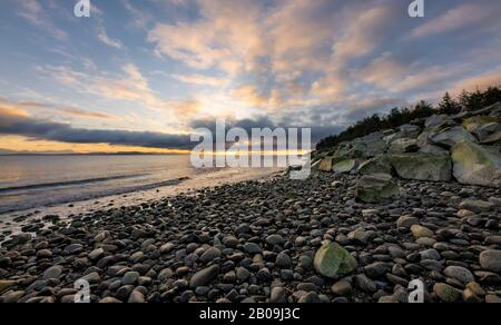 Beautiful dynamic sunrise over the coast with dramatic clouds over rocky beach on Vancouver Island, British Columbia, Canada - Stock Photo