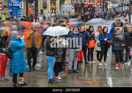 West End, London, UK. 19th Feb, 2020. Tourists on Piccadilly Circus make the most oft the weather. Tourists and Londoners make the most of short gaps in the rain on a wet but mild day in London's West End. Credit: Imageplotter/Alamy Live News - Stock Photo