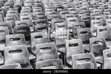 Rows of empty gray chairs in the rain, background. - Stock Photo