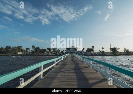 PINE ISLAND, FLORIDA - JAN 17, 2020. Woman reads a book on Bokeelia Pier in front of Fish House restaurant - Stock Photo