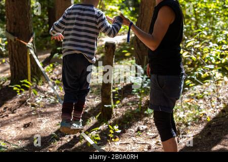 A caring mother is seen teaching a young boy how to balance on a slackline, anchored between two trees during a festival celebrating earth and culture - Stock Photo