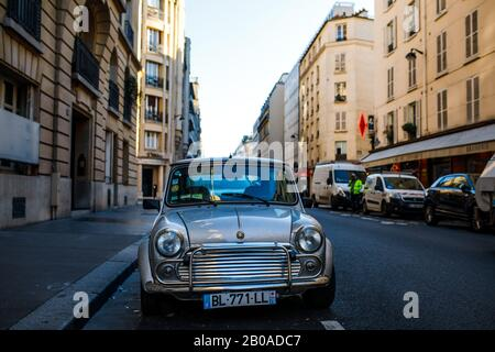 A small French car on a side street in Paris, France. - Stock Photo