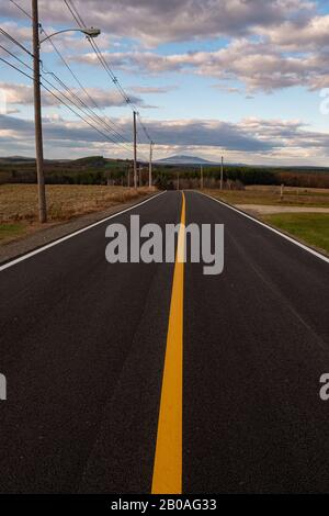 A newly paved road with a yellow line leading  us to Mt Monadnock off in the distance - Stock Photo