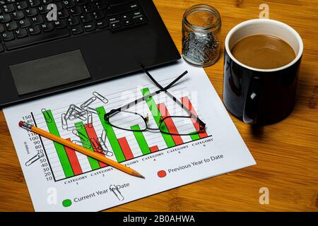 A business desktop space with a laptop, a cup of coffee, business papers, glasses and a pencil on a wooden desktop with paperclips scattered around. - Stock Photo