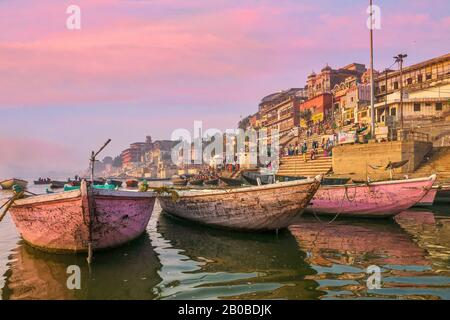 Varanasi, India - November 11, 2015. Wooden boats moored on the Ganges River, used for rowing tourists and Hindu pilgrims along the waterfront ghats. - Stock Photo