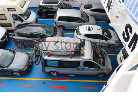 Cars and camper vans on a ferryboat to Sicily in the Strait of Messina, Italy - Stock Photo