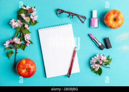 Spring turquoise layout with white notepad with pen, women's glasses, pink lipstick and nail polish, two apples and pink Apple tree twigs. Woman home - Stock Photo
