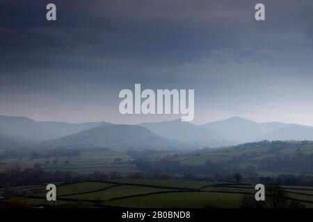 Hazy view across the Usk Valley to the peaks of Fan y Big, Cribyn and Pen y Fan in the Brecon Beacons, Wales, UK - Stock Photo
