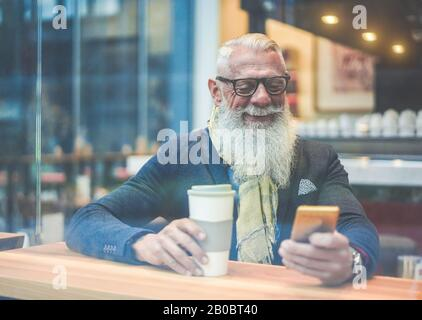 Senior business man using smartphone app while drinking coffee inside lounge bar - Hipster entrepreneur doing breakfast with cappuccino - Job, fashion - Stock Photo