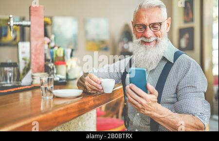 Happy senior man using smartphone app while drinking coffee inside vintage bar - Fashion old guy having fun with new trend technology - Tech and joyfu - Stock Photo