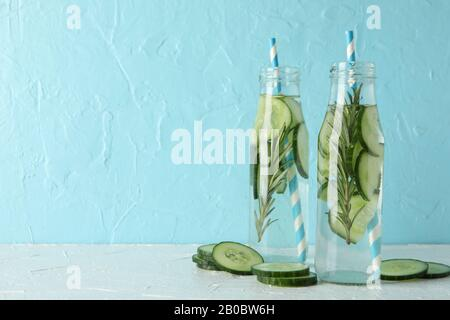 Composition with bottles of cucumber water against blue background, space for text - Stock Photo