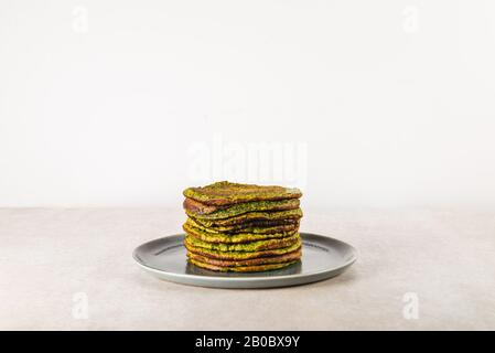 Healthy green pancakes made from spinach, coconut milk, banana and oats. Vegetarian and gluten free breakfast - Stock Photo