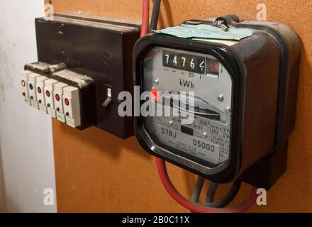 An old style mechanical electricity meter alongside a row of plug in fuses - Stock Photo