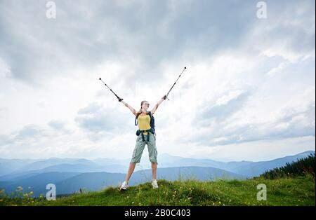 Happy woman hiker hiking mountain trail, standing on a top of grassy hill with raised hands, holding trekking sticks, wearing backpack and sunglasses, enjoying summer day. Outdoor activity concept - Stock Photo