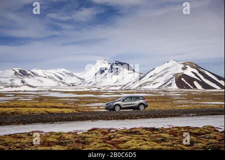 Motor car travelling through a snow covered, mountain landscape in Western Iceland