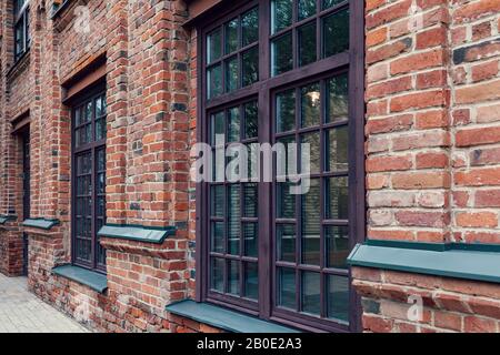Modern urban architecture; reconstruction of buildings of the old factory complex; brick walls and large windows of company offices. - Stock Photo