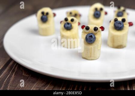 funny little banana bear figures on white plate healthy dessert for kids. - Stock Photo