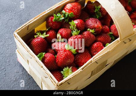 Fresh ripe strawberries in a wooden basket on a dark background. Organic juicy berries. Top view. Copy space for your text. Stock Photo