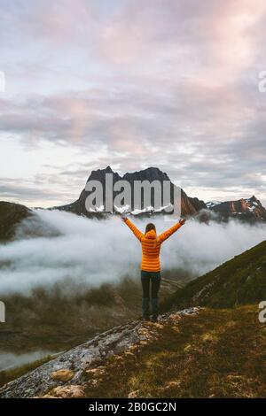 Woman enjoying landscape raised hands in mountains travel vacations adventure healthy lifestyle outdoor sustainable tourism in Norway summer activity - Stock Photo