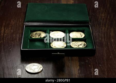 1 ounce American Buffalo gold bullion coins in a coin box on wooden background - Stock Photo