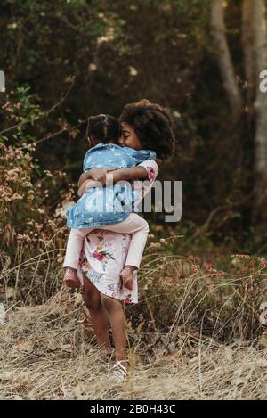 Portrait of two sisters hugging in backlit field - Stock Photo