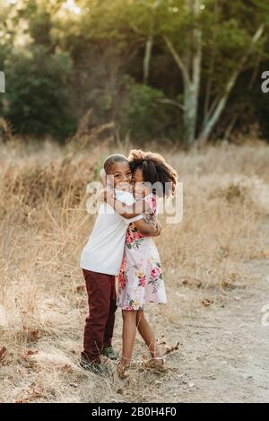 Portrait of two sun-kissed siblings smiling at camera field - Stock Photo