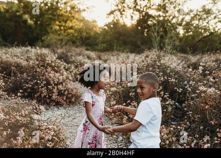 Close up view of brother and sister holding hands and playing