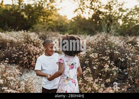 Close up view of brother and sister holding hands and playing in field
