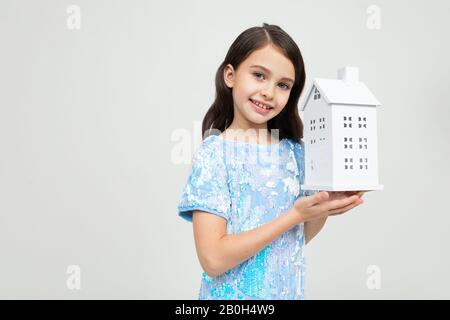 teenager girl with a model of the house in hands on a white background with copy space. immovable property. - Stock Photo