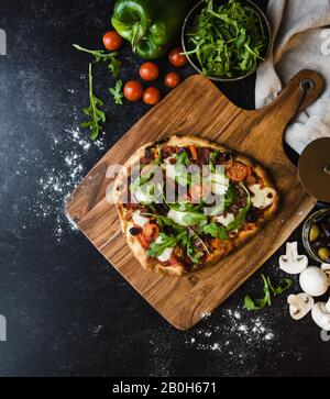 Top view of handmade pizza on wooden board with ingredients around it.