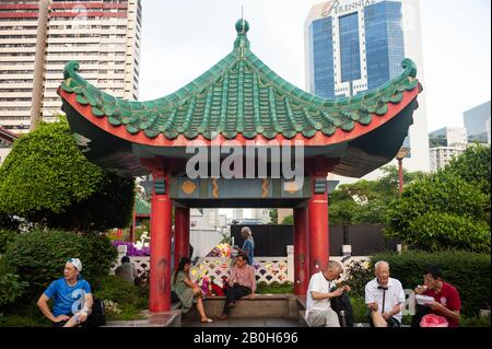23.01.2020, Singapore, , Singapore - People sit in a small public park under a roof in the form of a pagoda, which leads across New Bridge Road and Eu