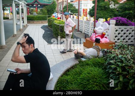 23.01.2020, Singapore, , Singapore - Three men in a small public park, which leads over New Bridge Road and Eu Tong Sen Street in the Chinatown distri